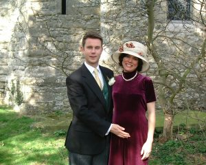 "The happy parents-to-be at a typical English wedding, with Katy admittedly ""thankful that my hat took a little of the focus off my belly."""